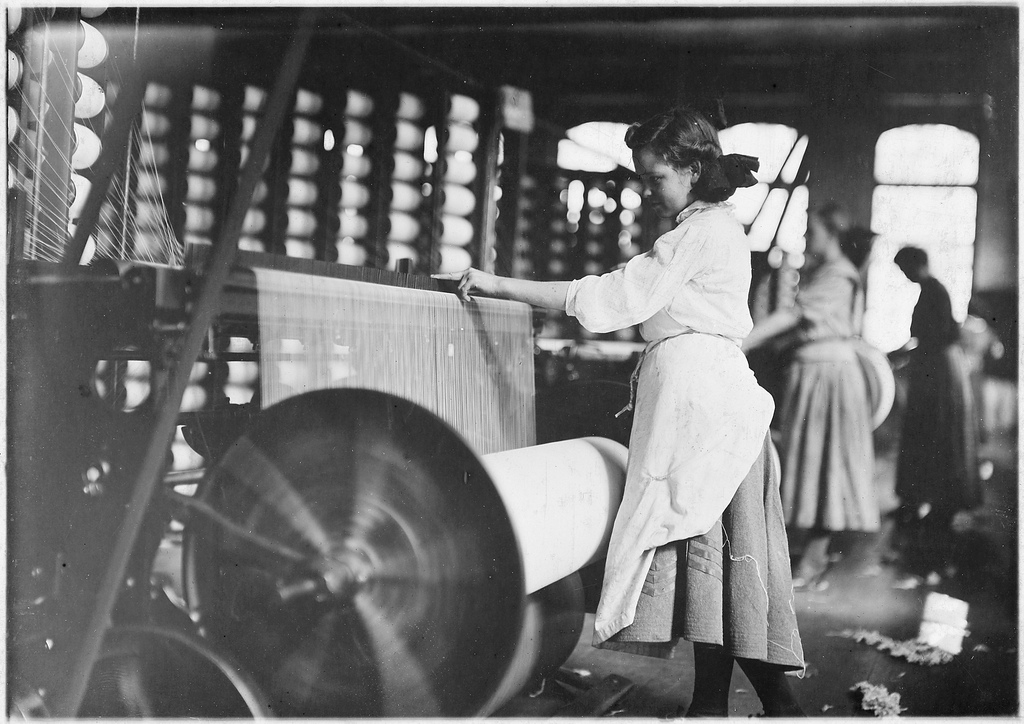 Girls at Weaving Machines, Evansville, Ind. (1908). Image by Lewis Hine via National Archives and Records Administration.