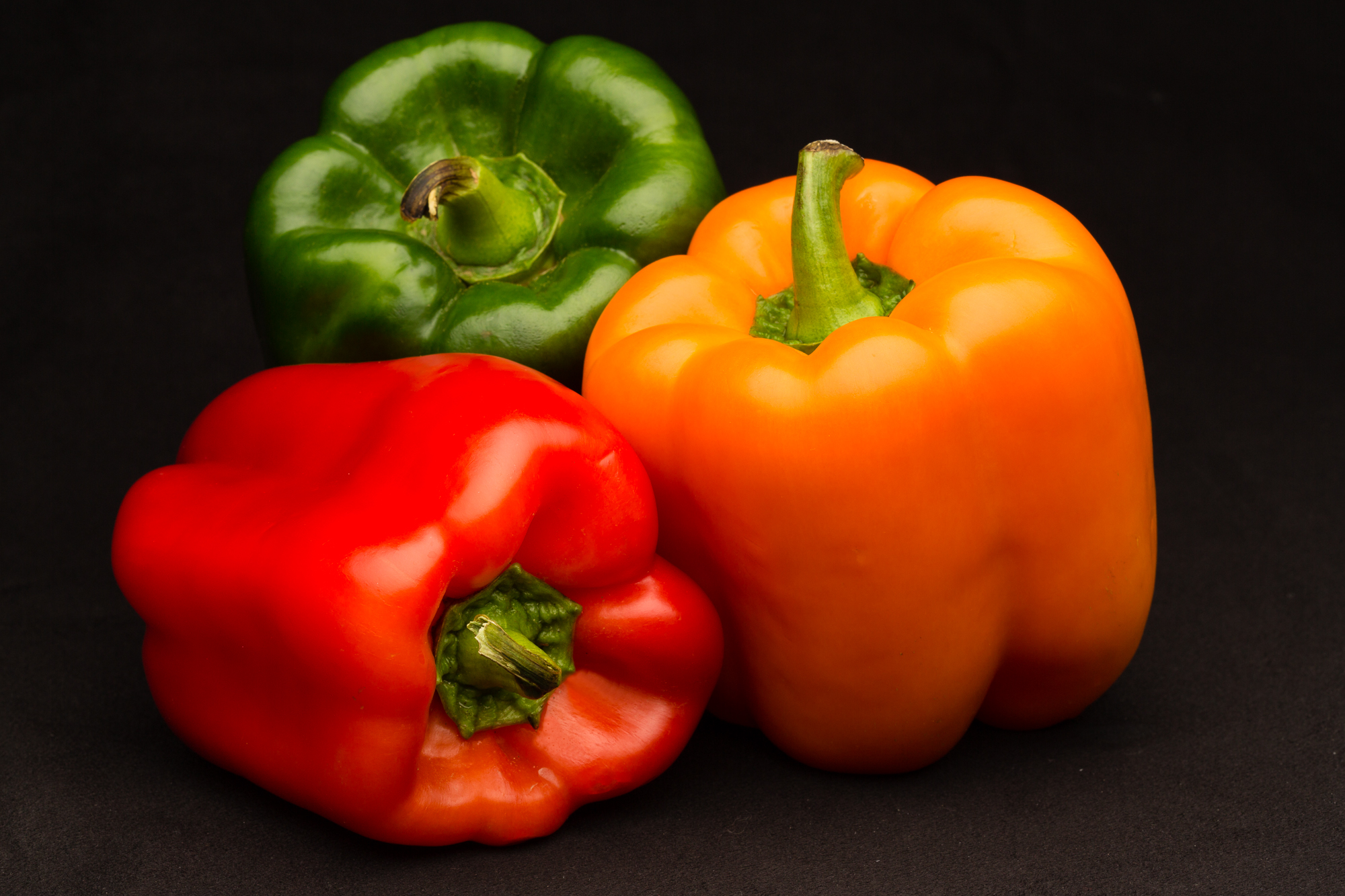 Professional food photo of red, green and orange bell peppers. Commercial photography
