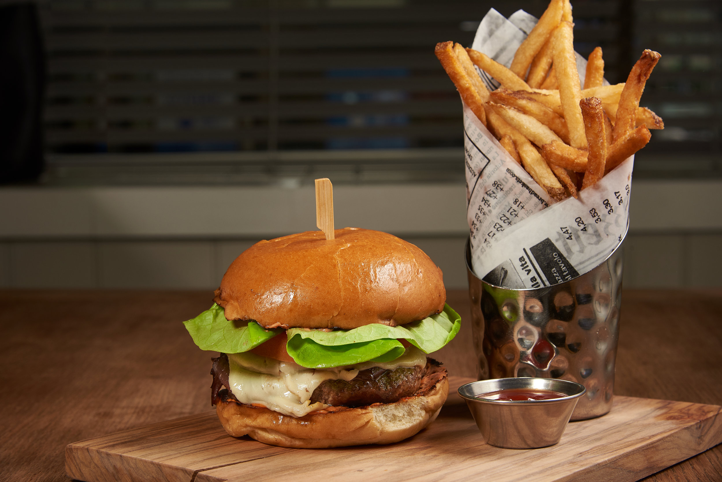 Professional food photo of a juicy cheese burger with french fries. Commercial photography