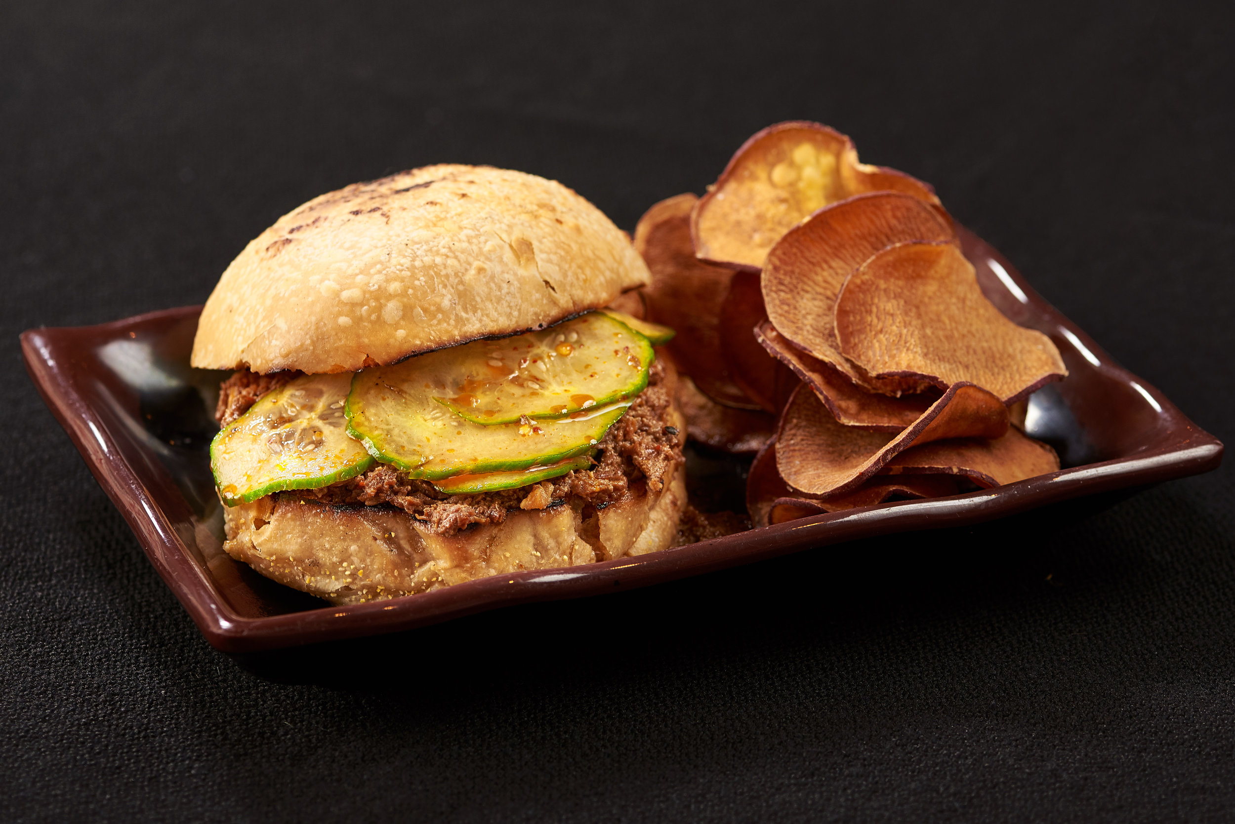 Professional food photo of pulled pork sandwich with pickles and potato chips. Commercial photography