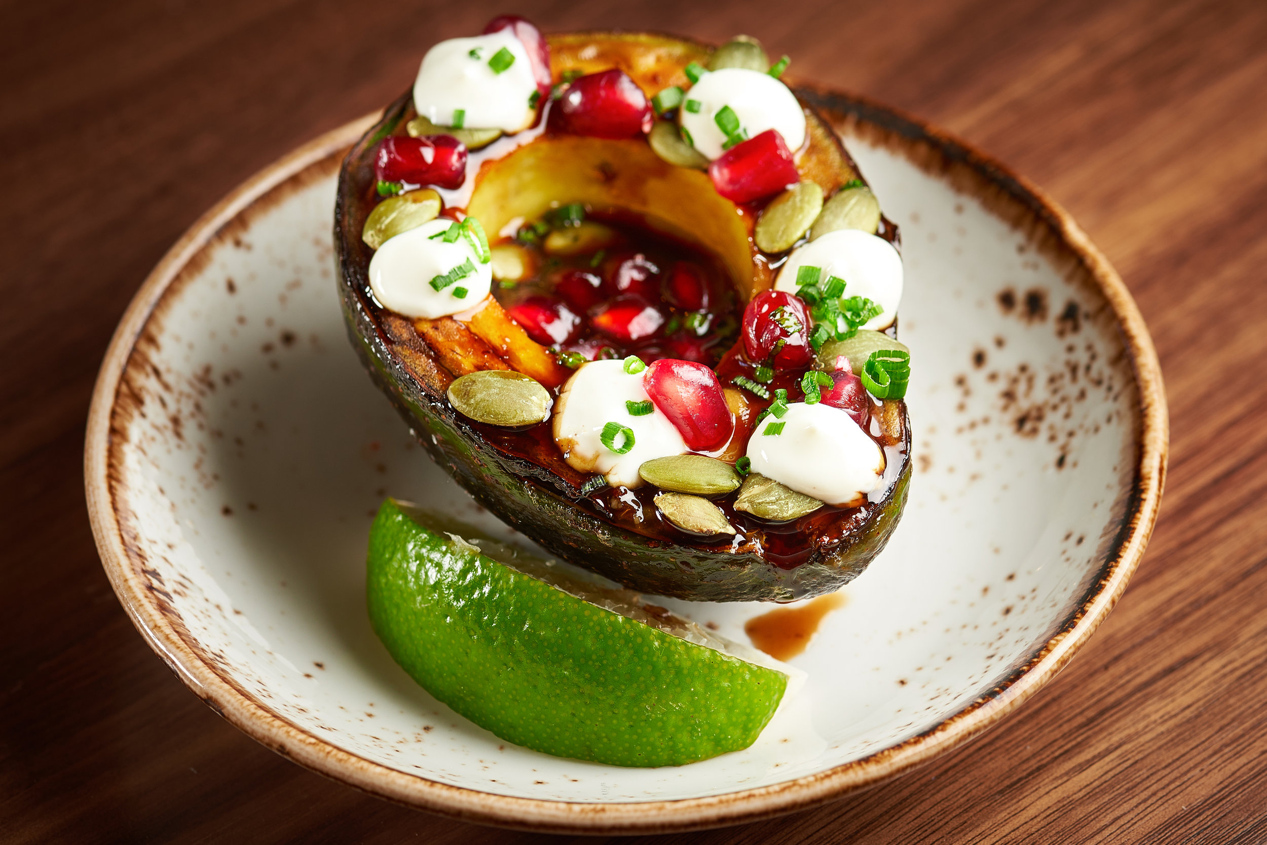 Professional food photo of grilled avocado salad with pomegranate and cheese. Commercial photography