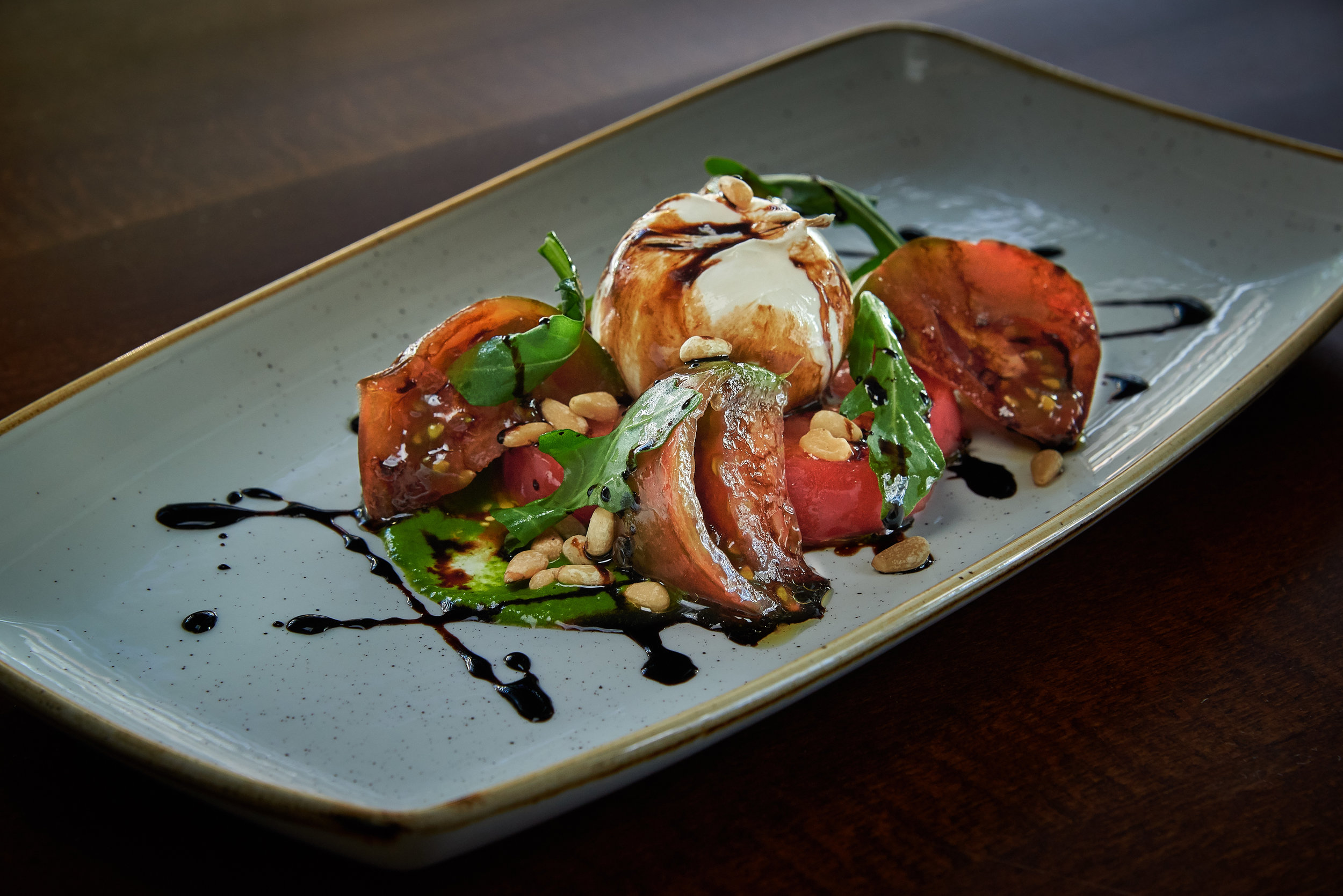 Professional food photo of a delicious salad made with tomato, arugula, pine nuts, fresh mozzarella and balsamic vinegar. Commercial photography
