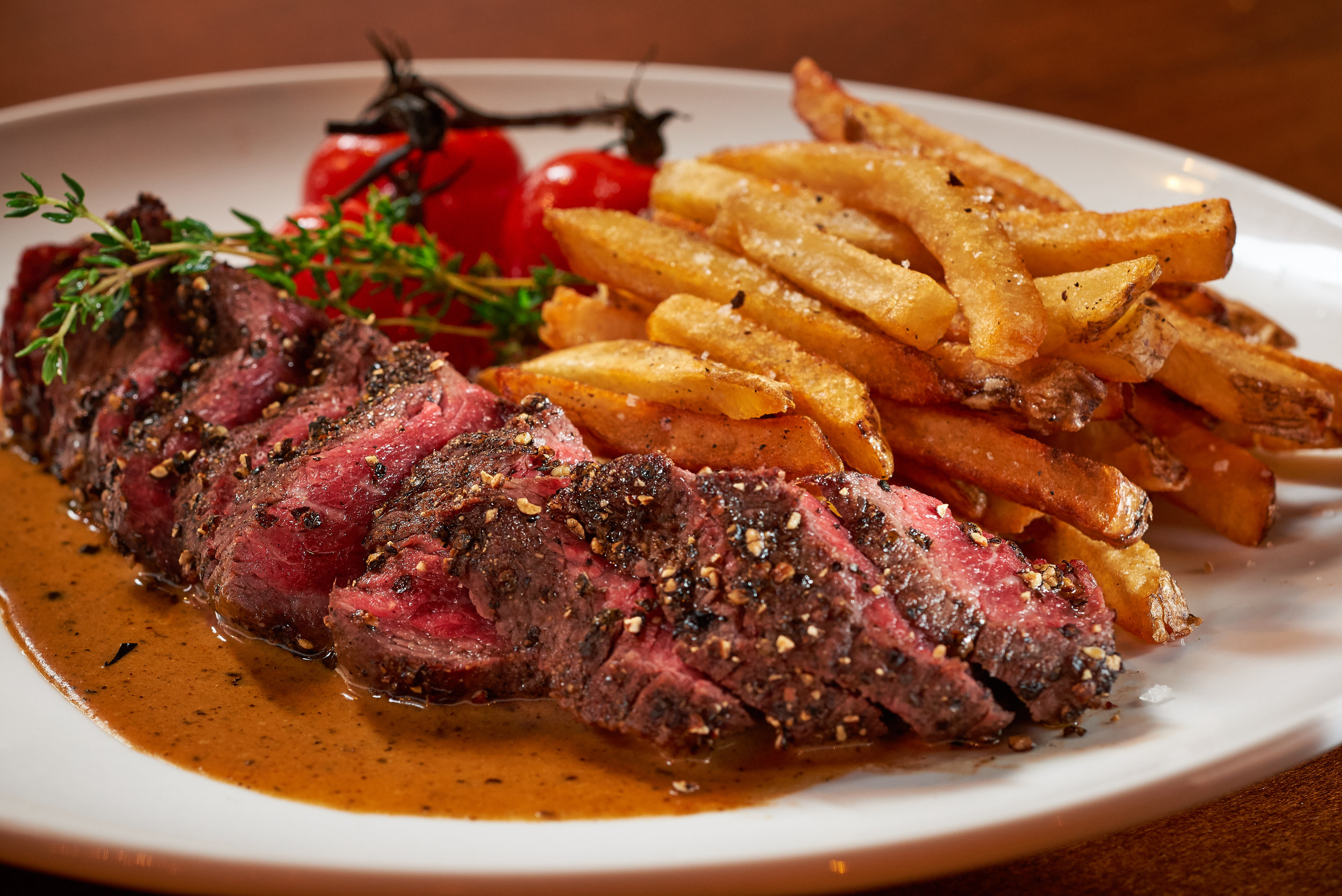 Professional food photo of juicy medium rare steak with french fries and grape tomatoes. Commercial photography