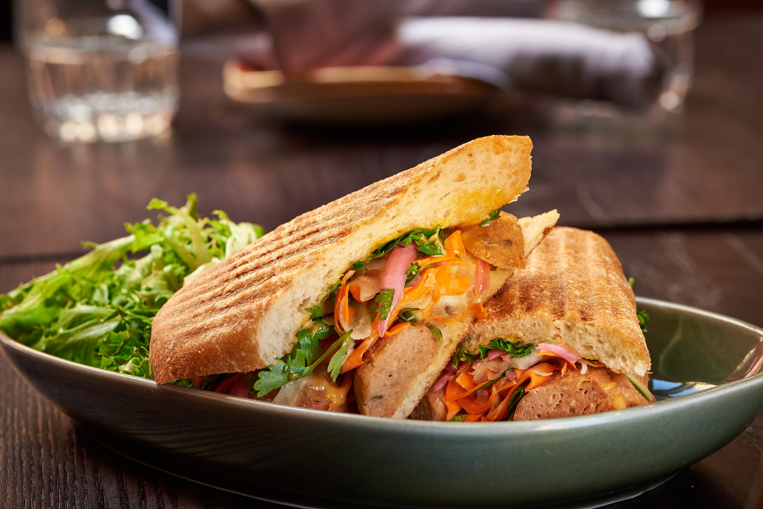 Professional food photo of a meatball panini sandwich made with cilantro, pickle onions and cheese with salad on the side. Commercial photography