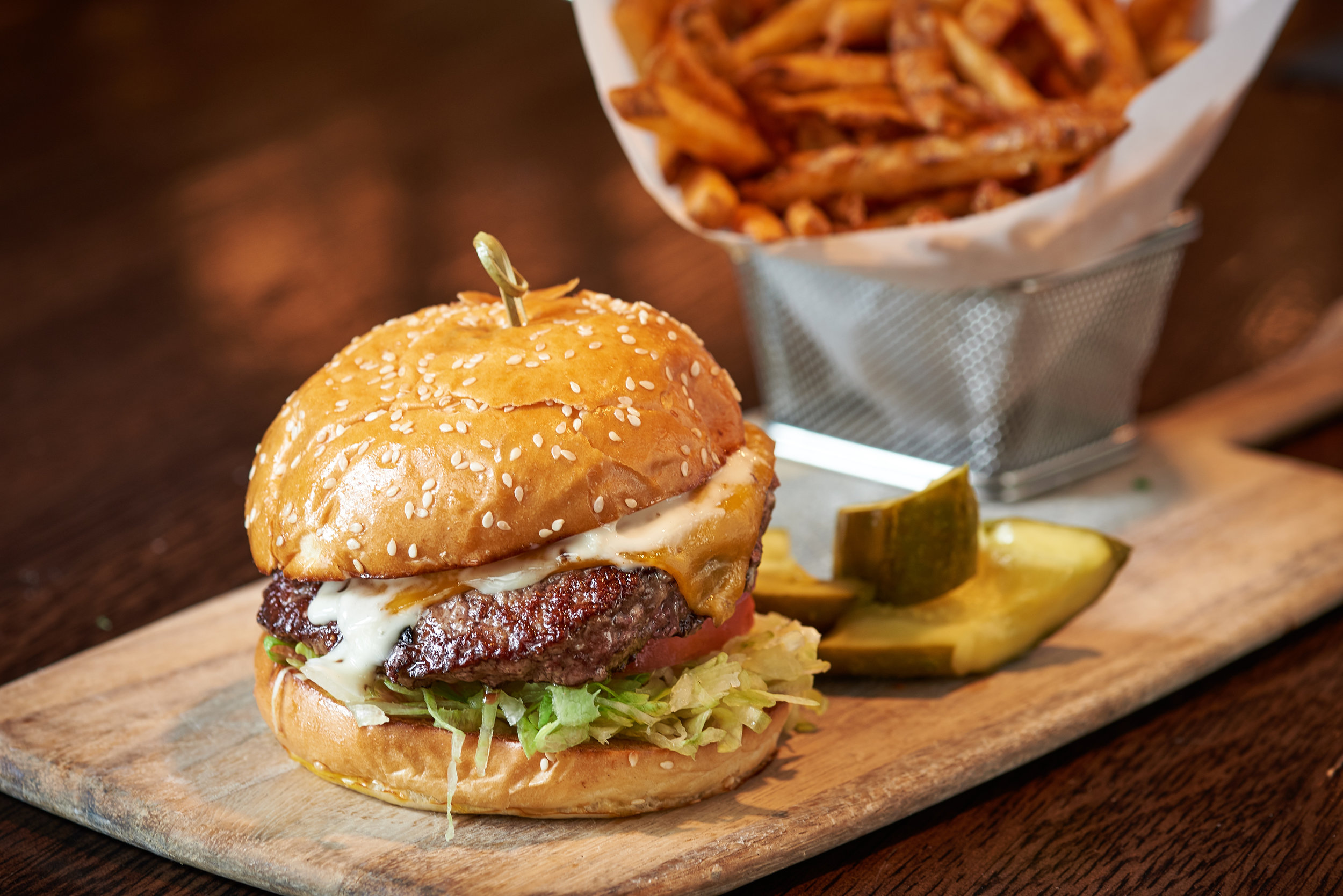 Professional food photo of a juicy cheese burger with french fries and pickles on the side. Commercial photography