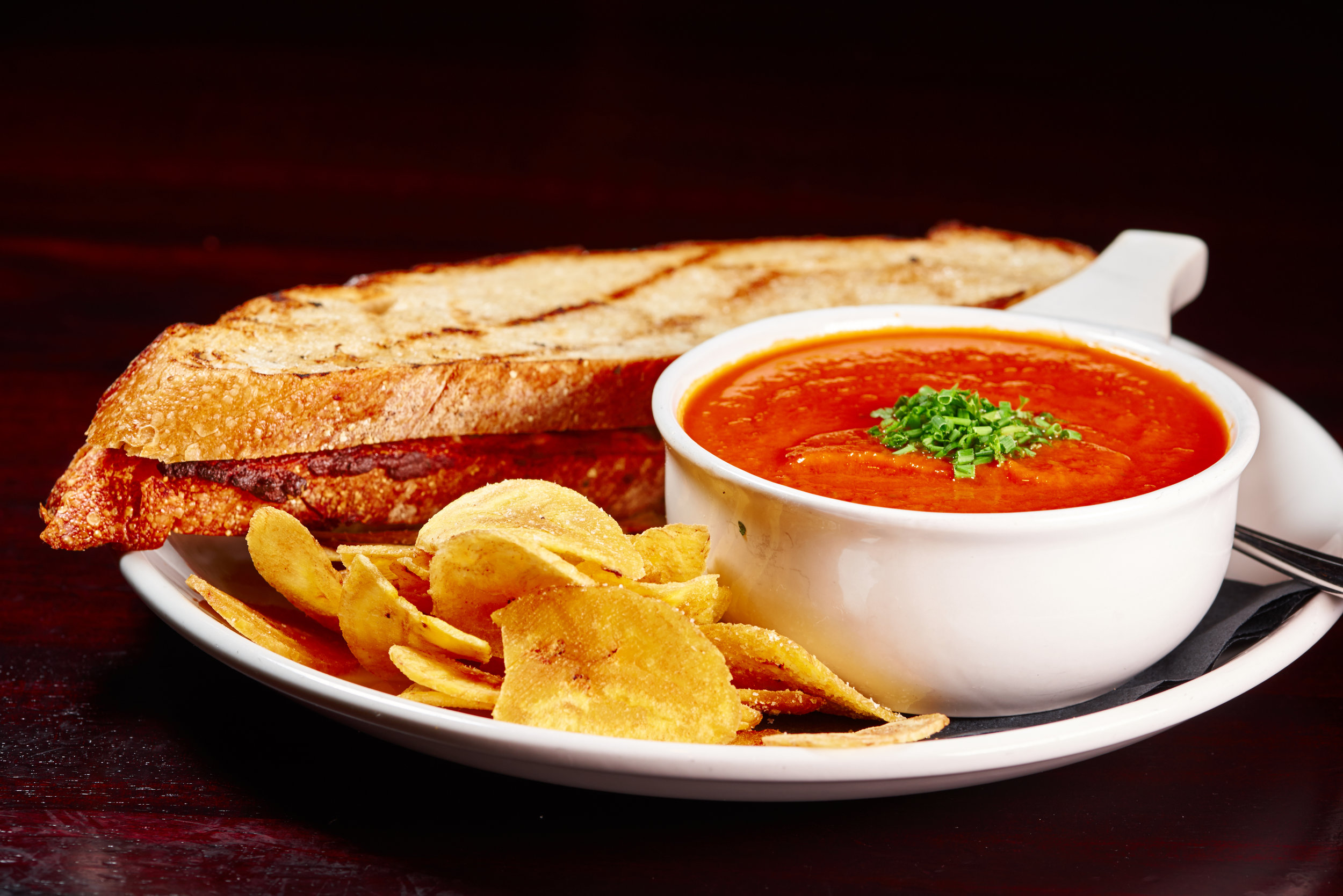 Professional food photo of a grilled cheese sandwich with tomato soup and potato chips on the side. Commercial photography. Photo taken by Lupa Photography