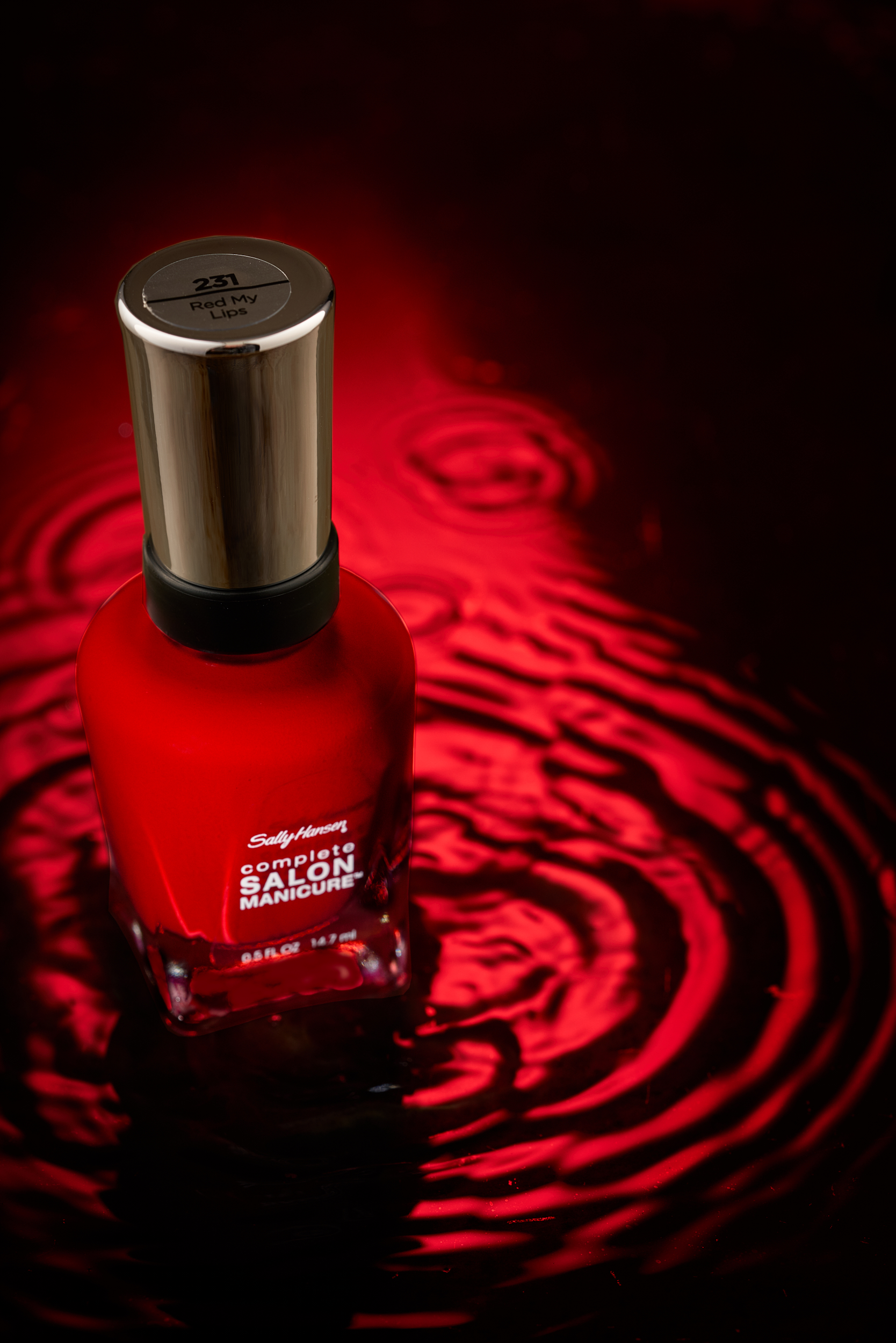 Professional commercial photograph of red nail polish on top of water.