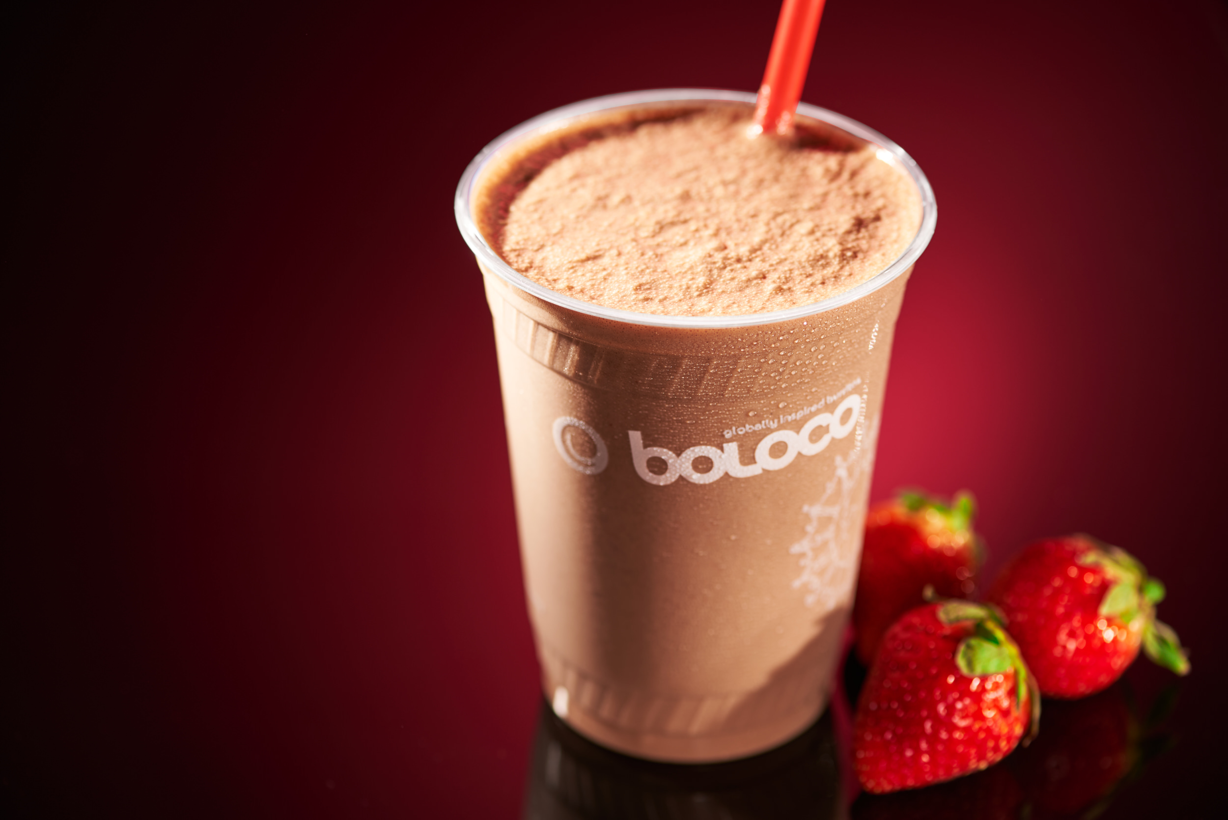 Professional picture of a strawberry and chocolate smoothie. Red background with strawberries next to the smoothie.