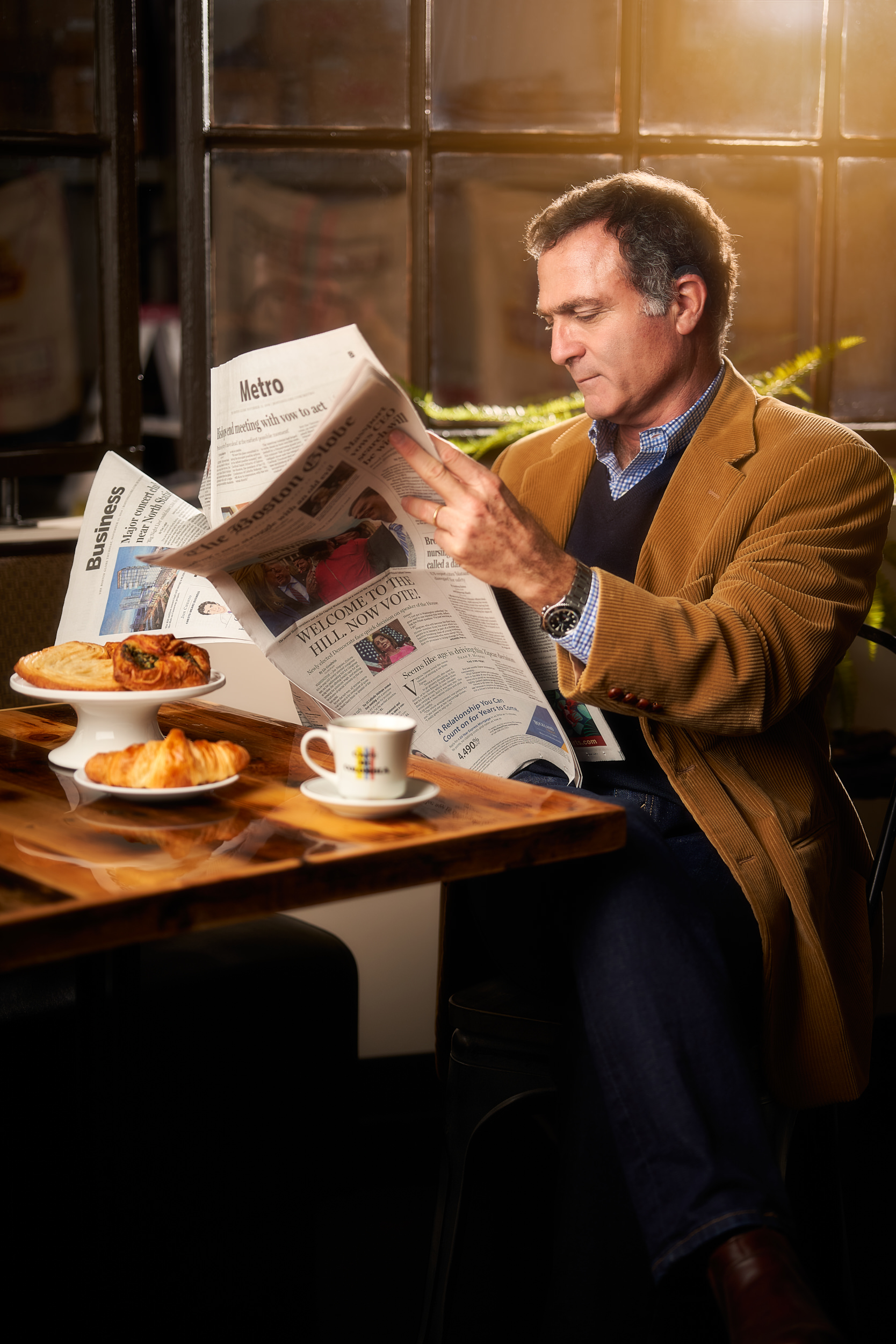 Professional staged picture of a man having breakfast and reading the news paper. For breakfast he is having coffee, croissant and other pastry