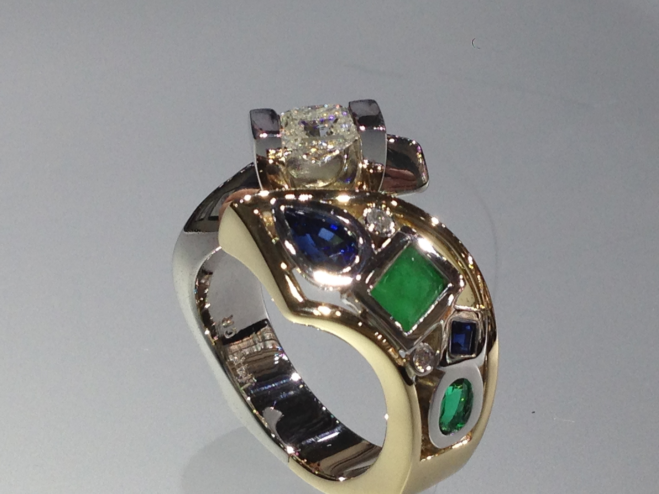 side-view-unique-pear-shape-sapphire-princess-cut-oval-emerald-princess-cut-diamond-unique-engagement-ring-craft-revival-jewelry-store-grand-rapids