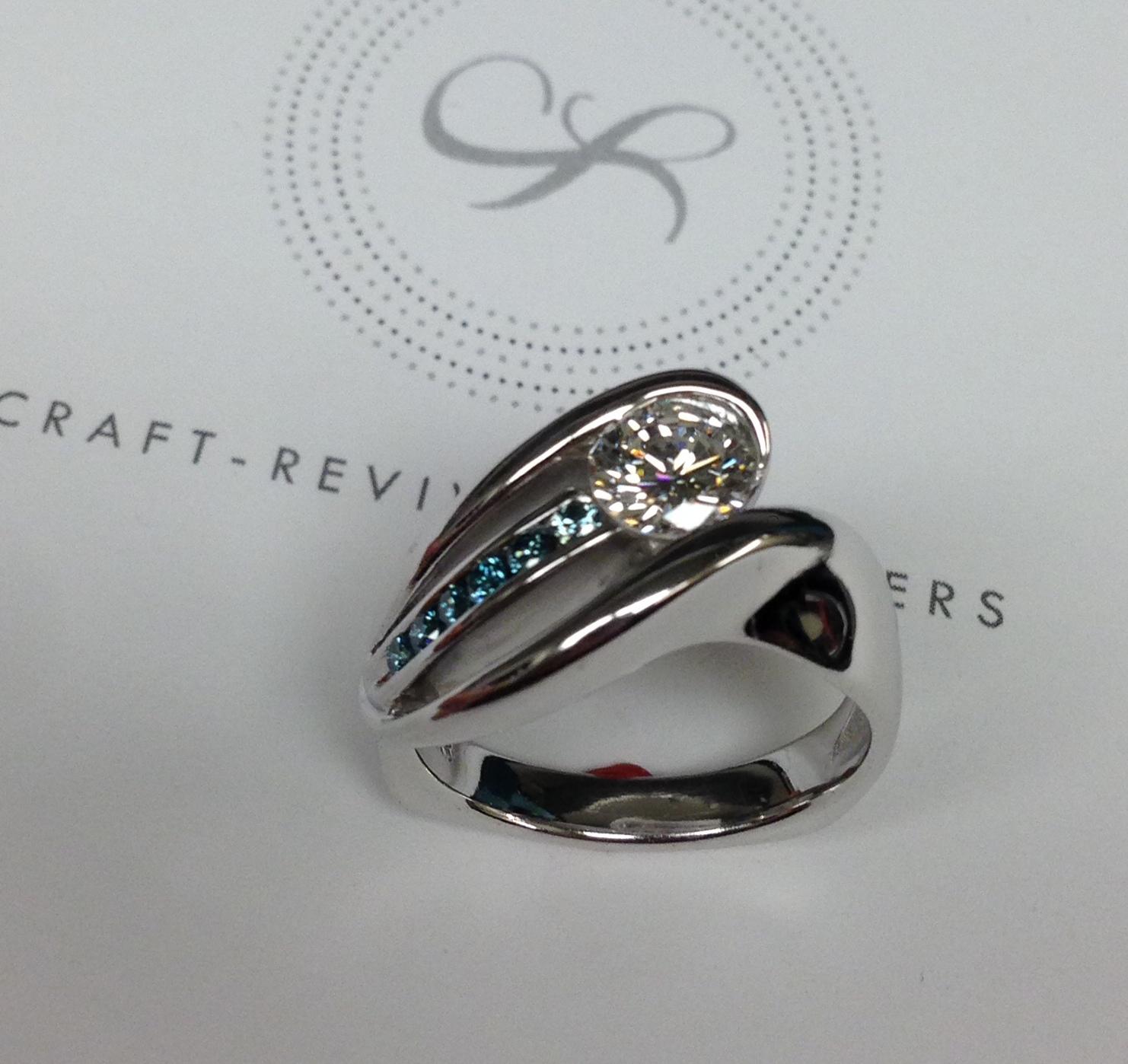 unique-custom-roud-diamond-blue-diamonds-modern-design-white-gold-engagement-ring-craft-revival-jewelry-store-grand-rapids