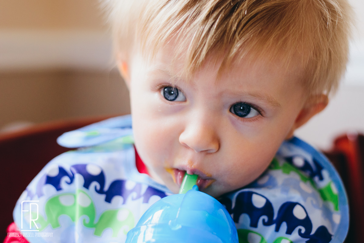 He's not really into solid food, but he has figured out drinking from a straw cup.