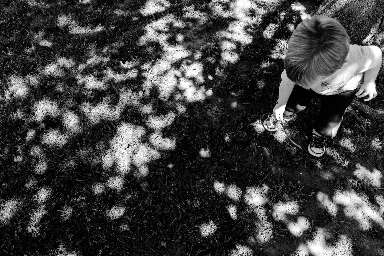 Logan playing under a tree at nursery school.