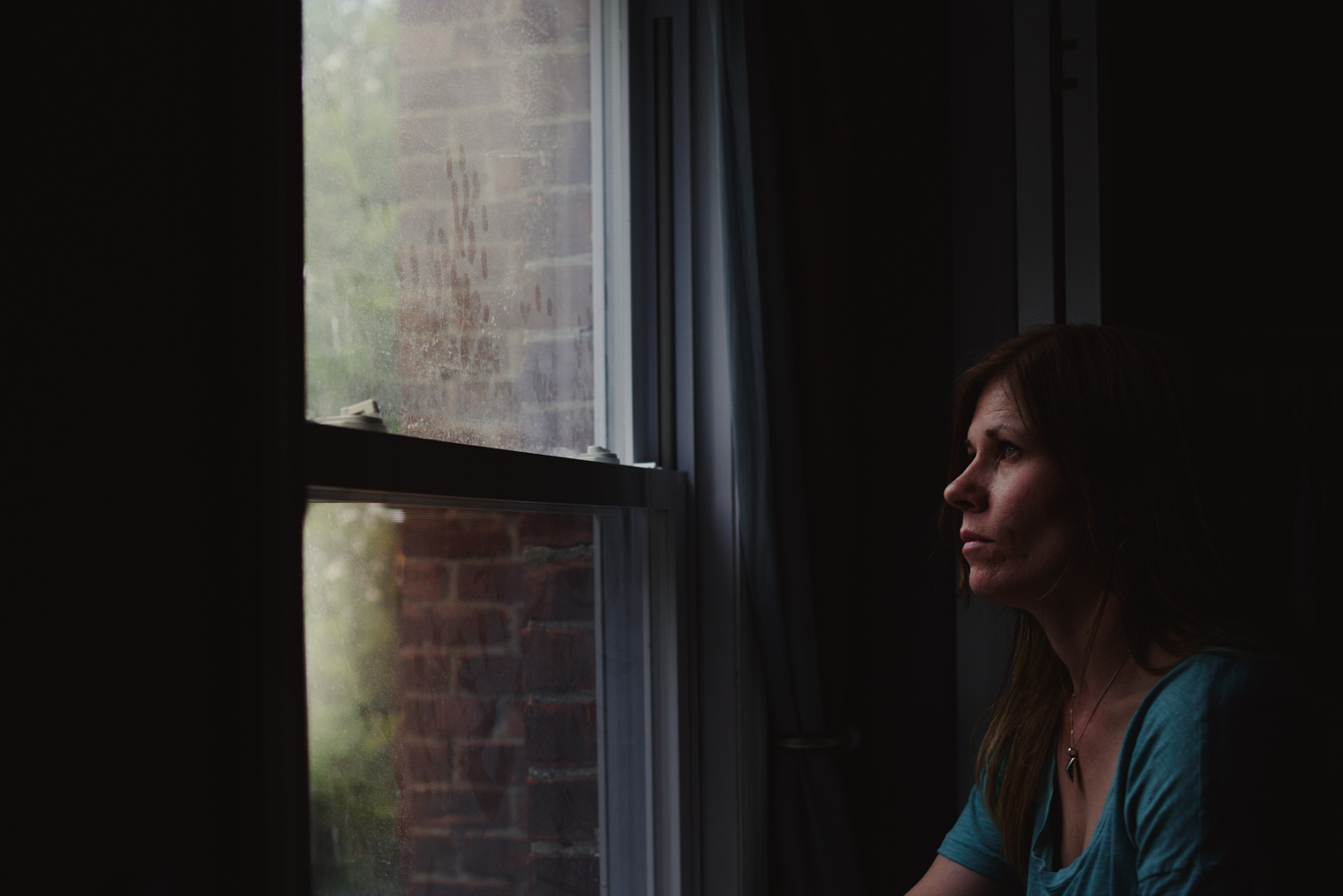 Woman looks out window | Francesca Russell Photography | Nassau County Photographer