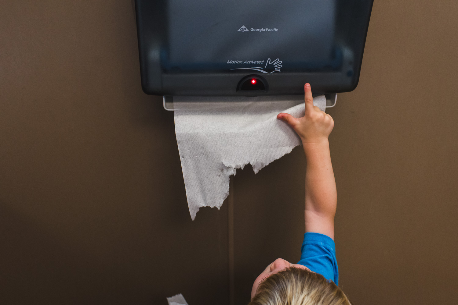 Little boy playing with automatic paper towel dispenser.