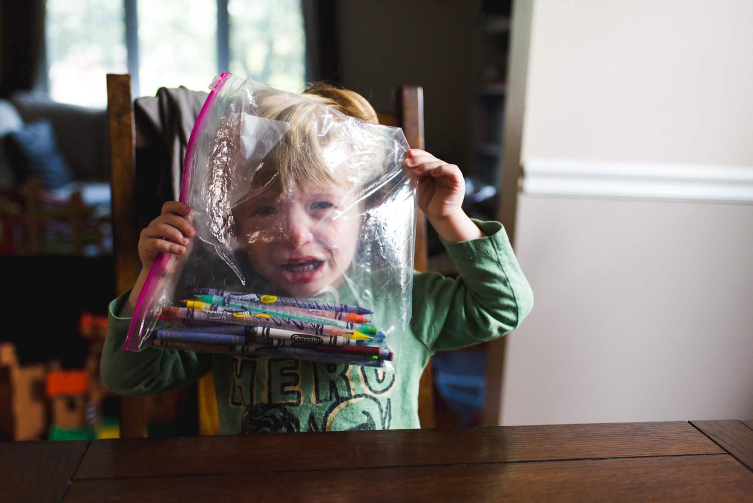 Little boy crying with plastic bag in front of face.