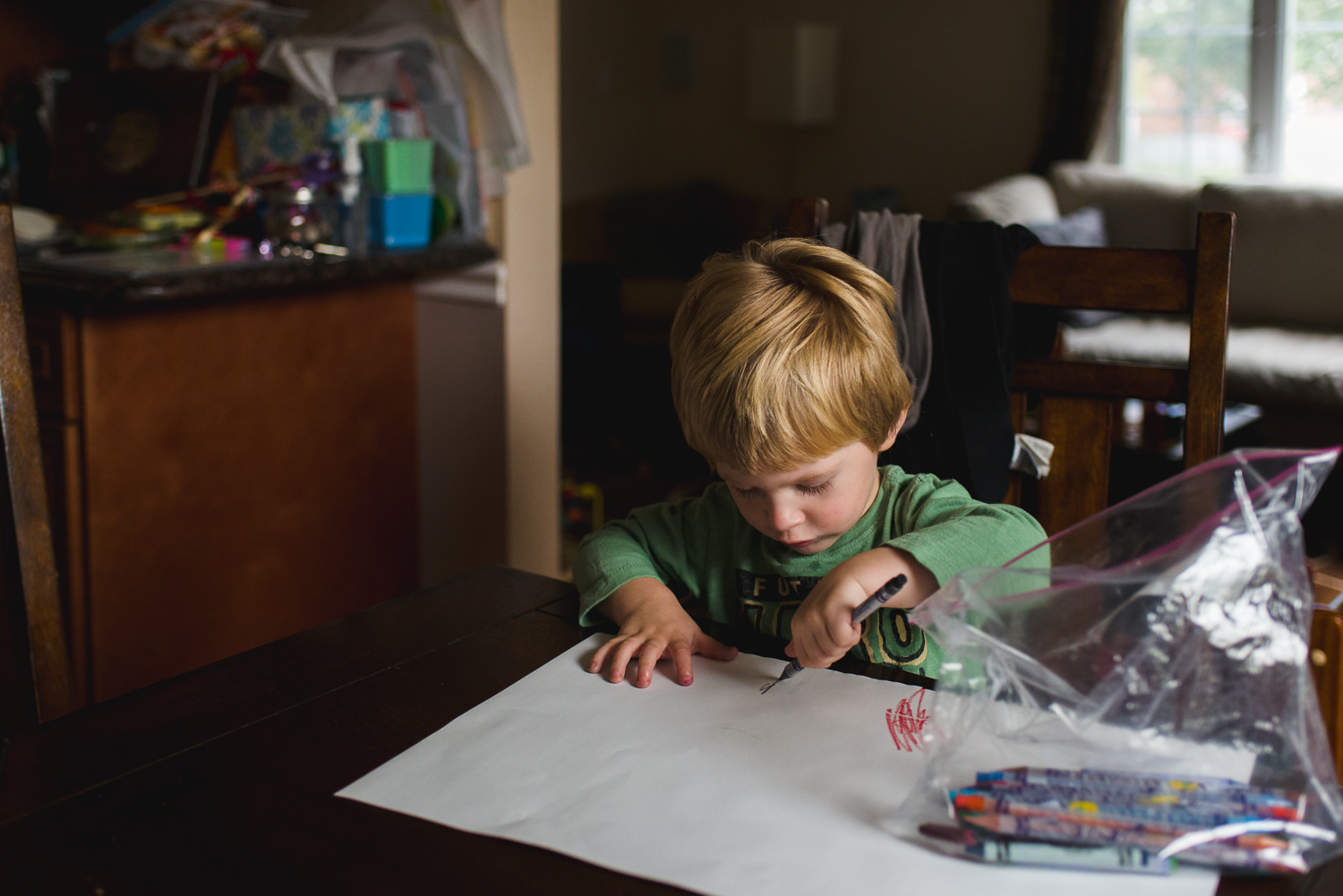 Little boy drawing at table.