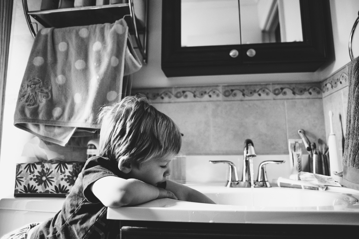 Toddler boy playing in the bathroom sink.