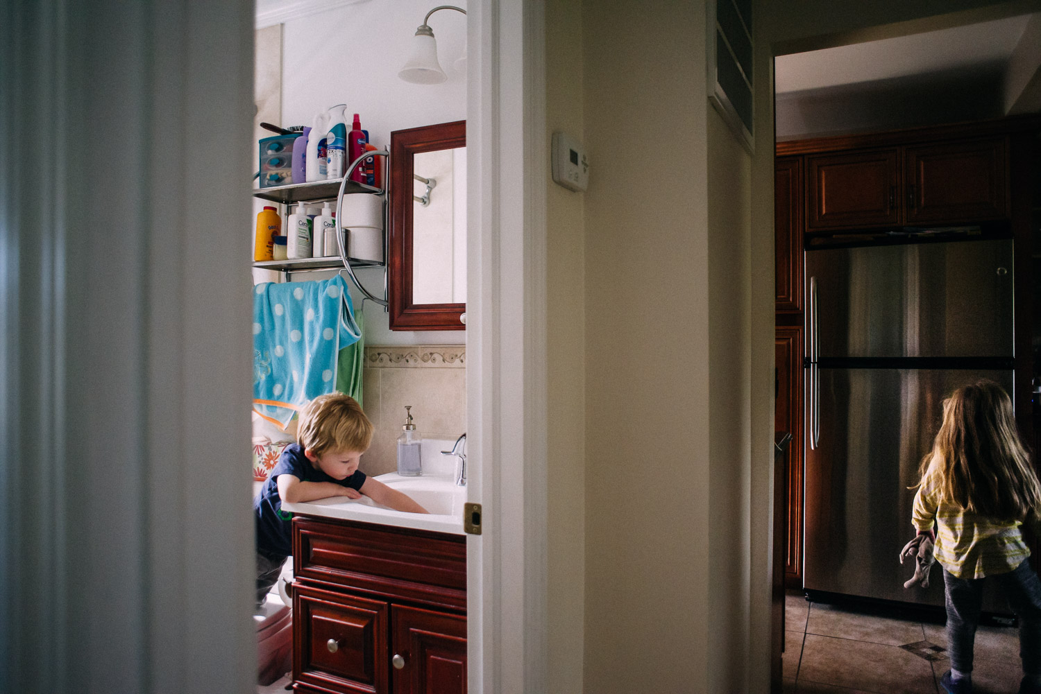Little boy in bathroom and sister in kitchen.