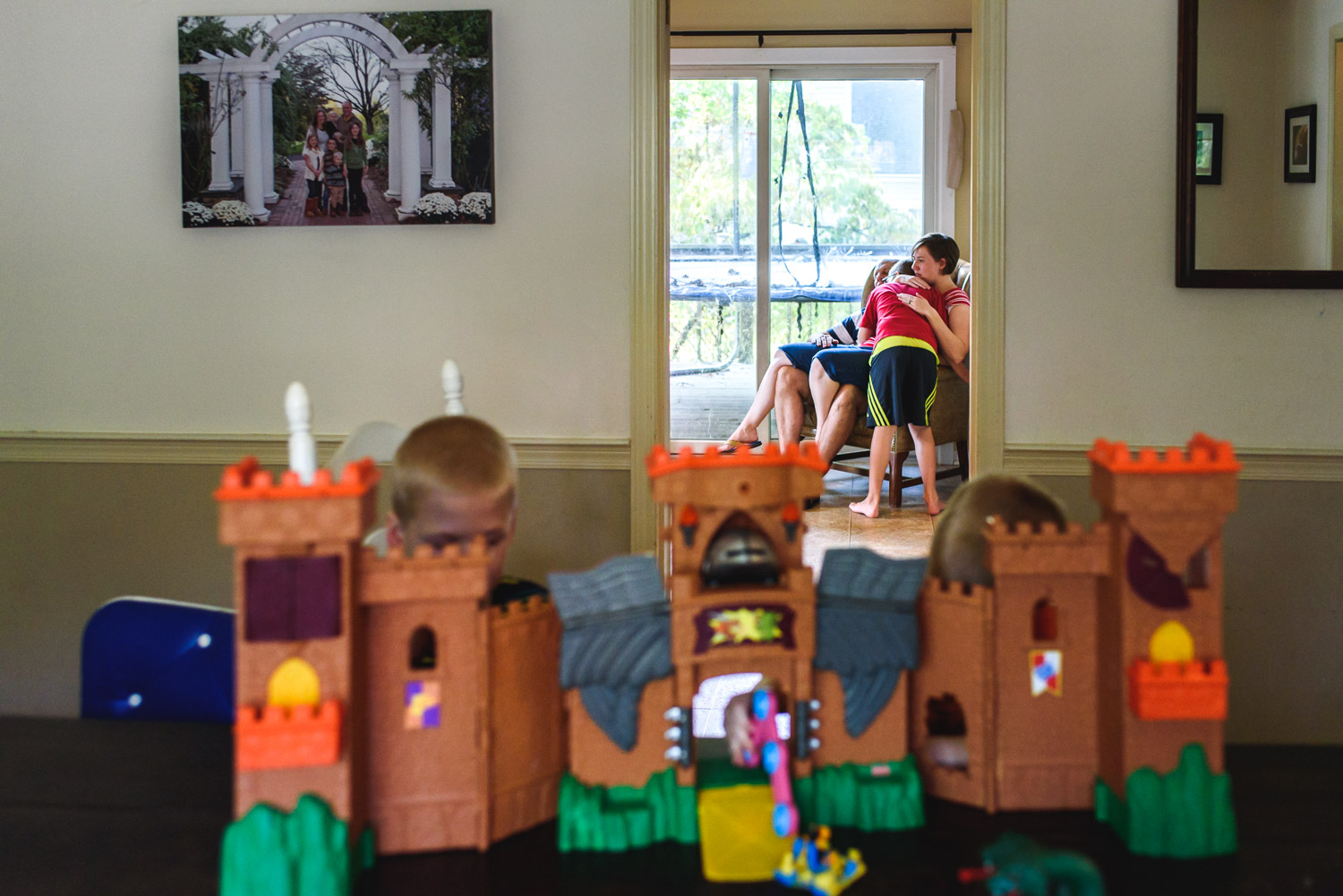 Kids playing with toy castle with mother in the background.