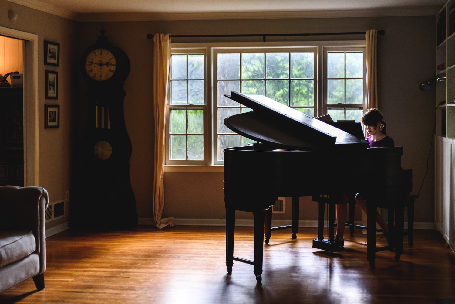 Teenage girl playing a grand piano.