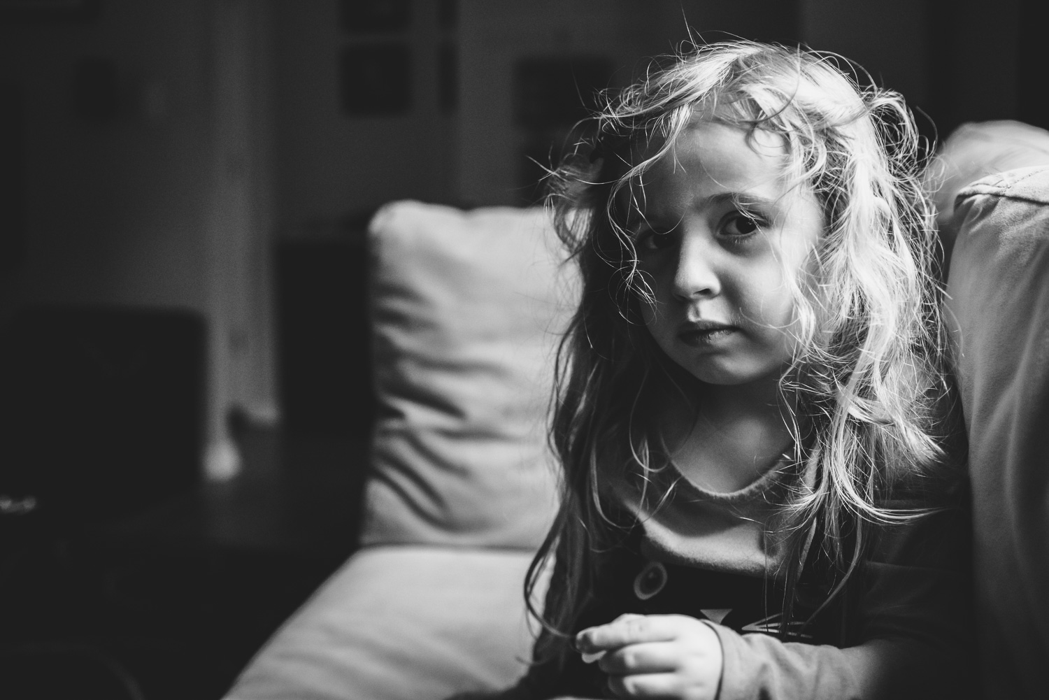 Portrait of a little girl sitting on couch.