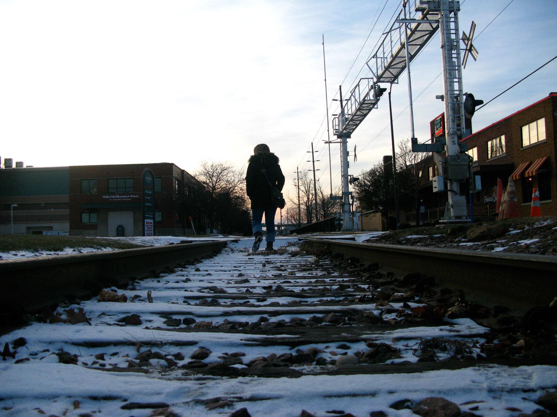 Woman walking on snowy train track.