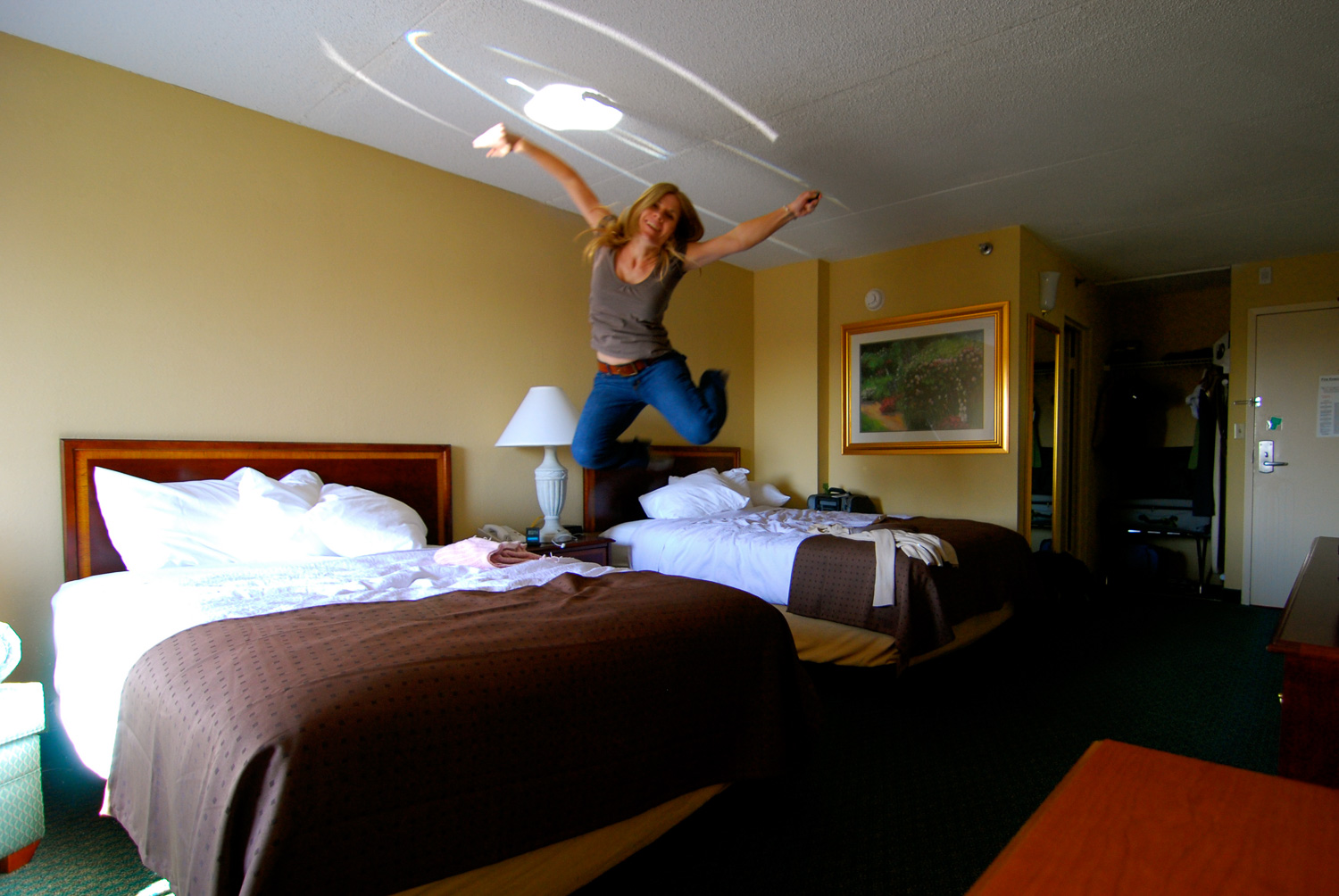 Woman jumping on hotel bed.