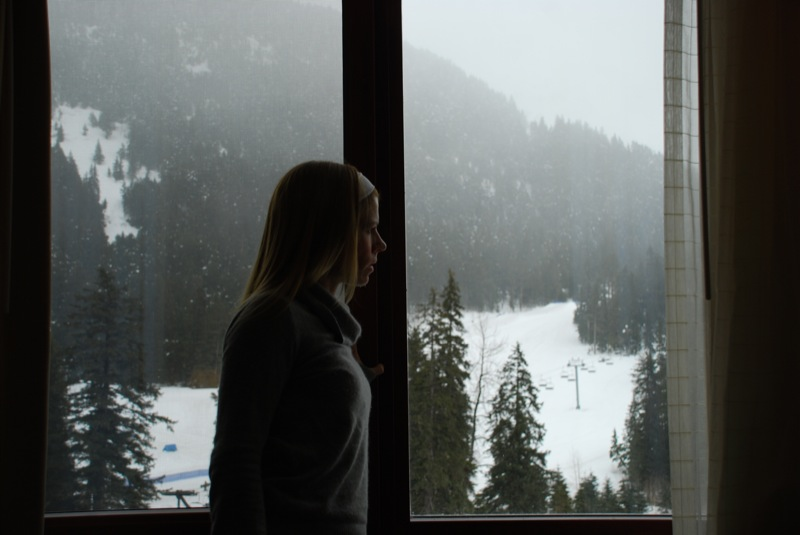 Woman looking out snowy window.