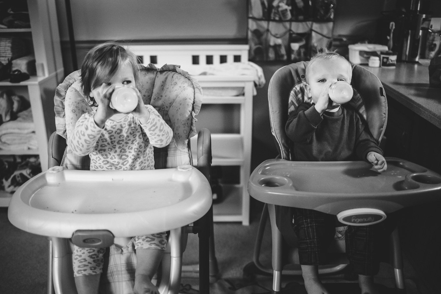 Twin babies in high chairs.
