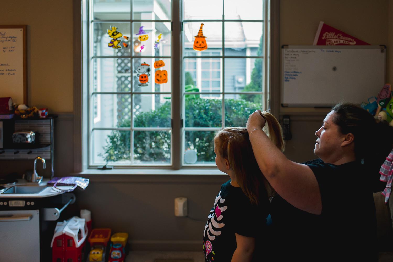 Mother brushing daughter's hair.