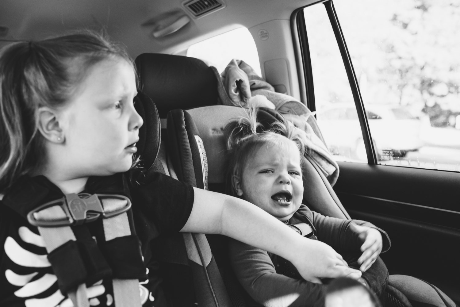 Little girl comforting crying baby in car.