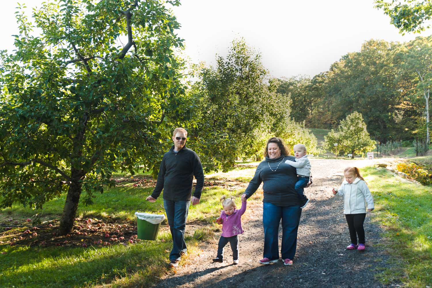 Family walking through an apple orchard.