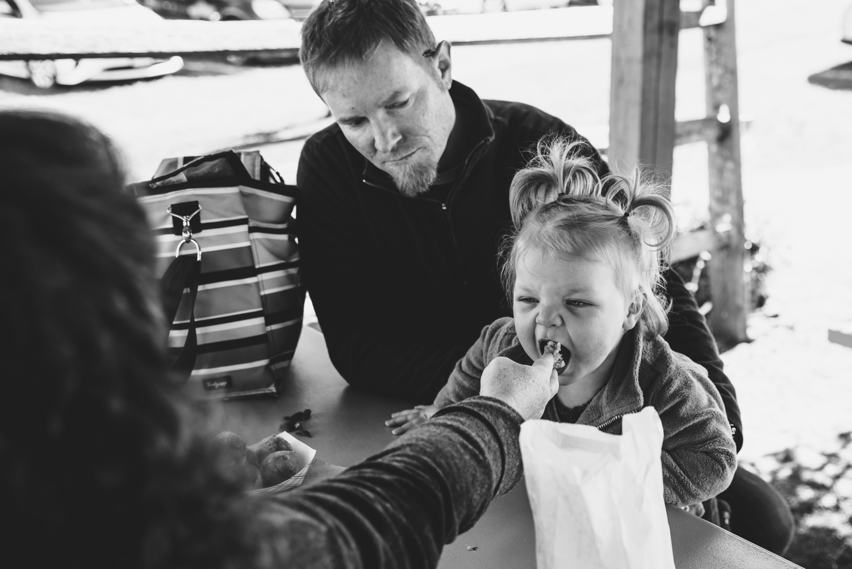 Feeding toddler daughter an apple fritter.
