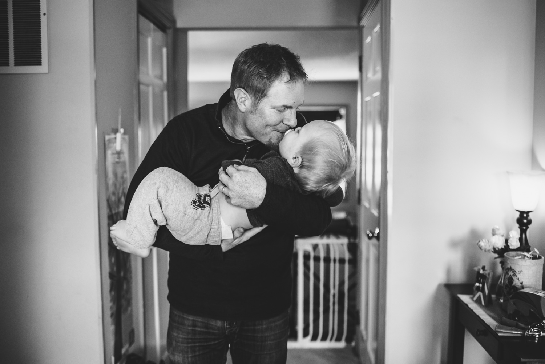 Dad kissing toddler son.