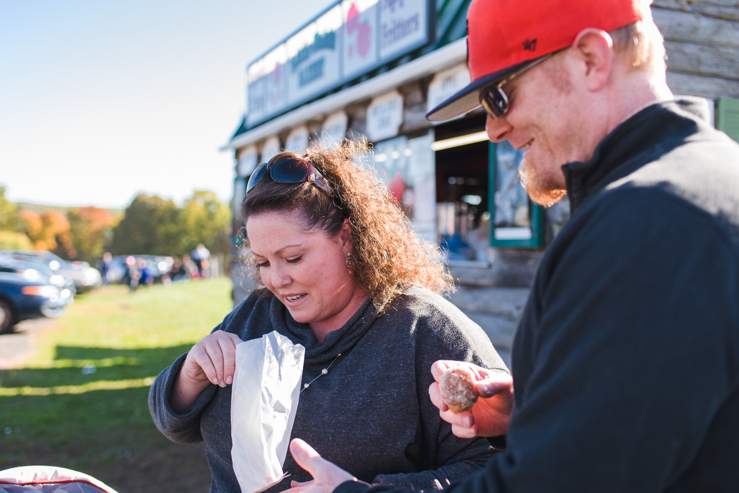 Couple eating apple fritters at an apple farm.
