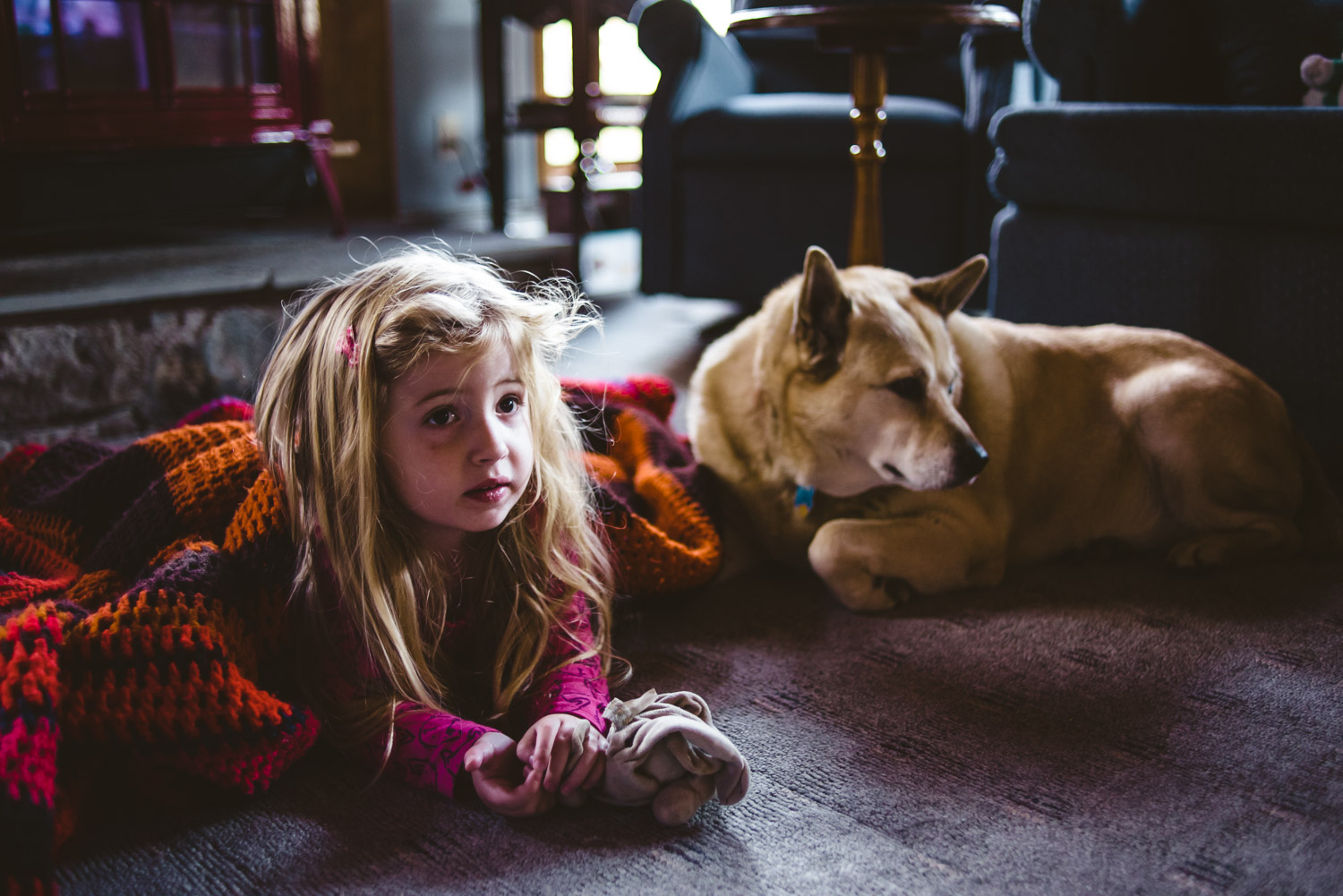 Little girl and dog sit by the fire.