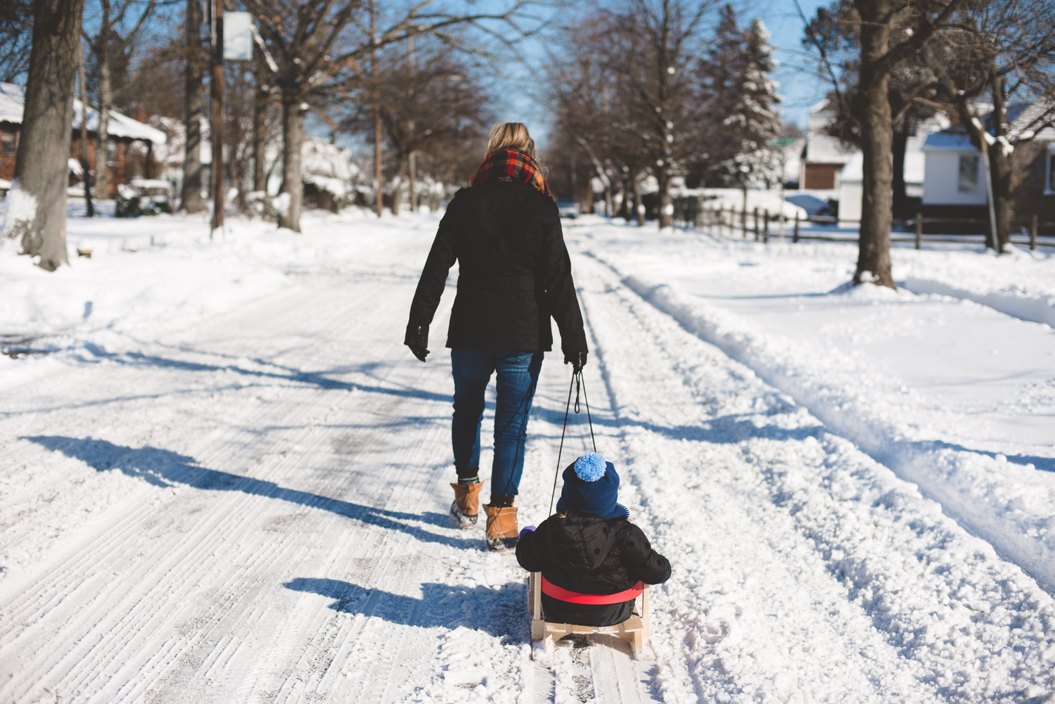 Woman pulling child on sled.