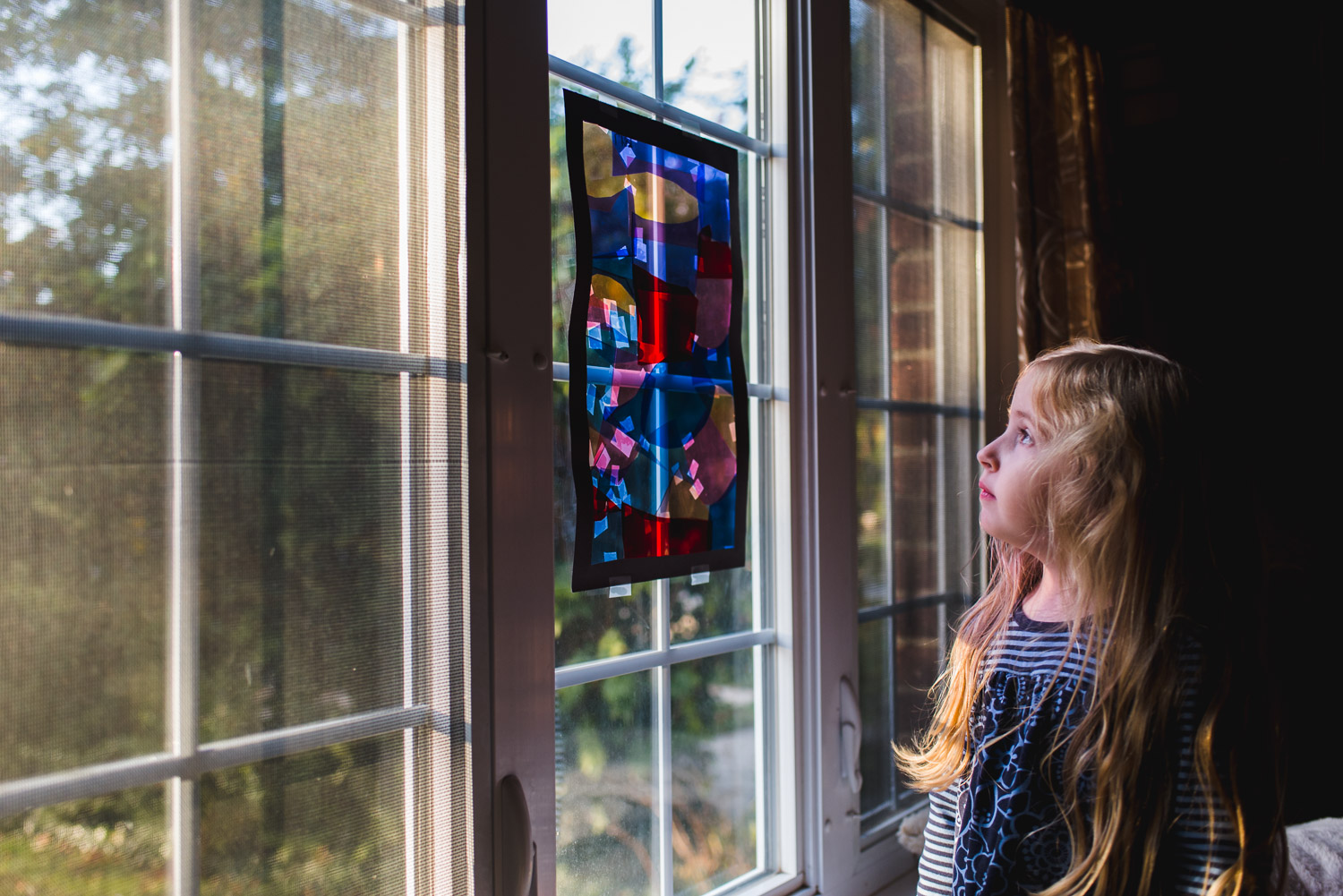 Little girl looking out stained glass window.