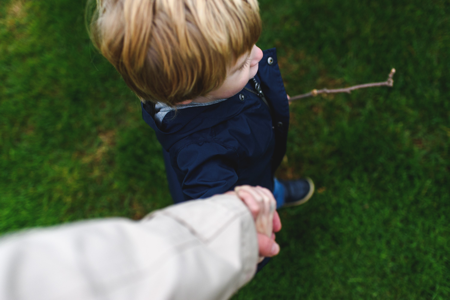 Little boy holding mother's hand.