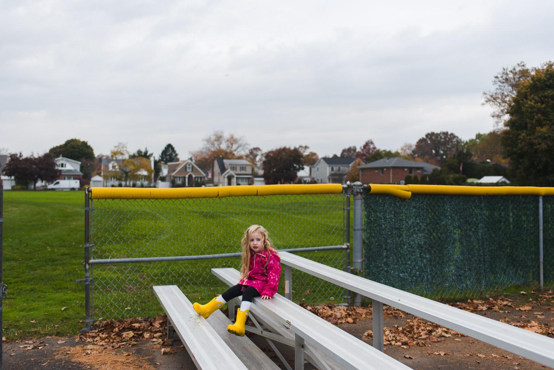 Little girl sitting on bleachers.