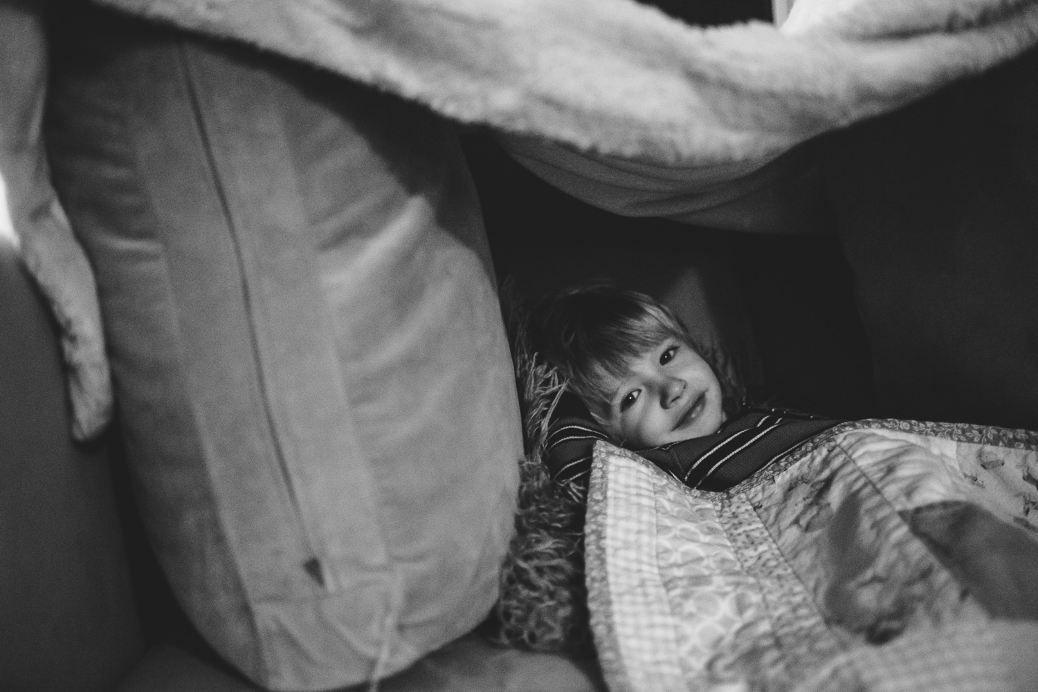 Little boy hiding in couch fort.