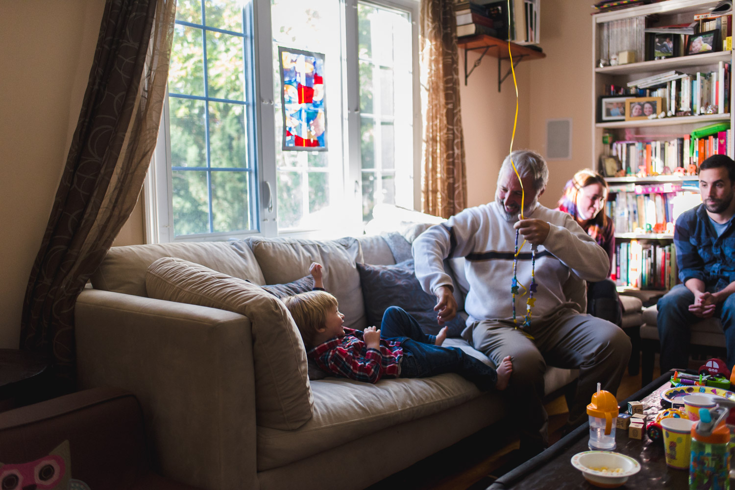 Grandfather playing with grandson on the couch.
