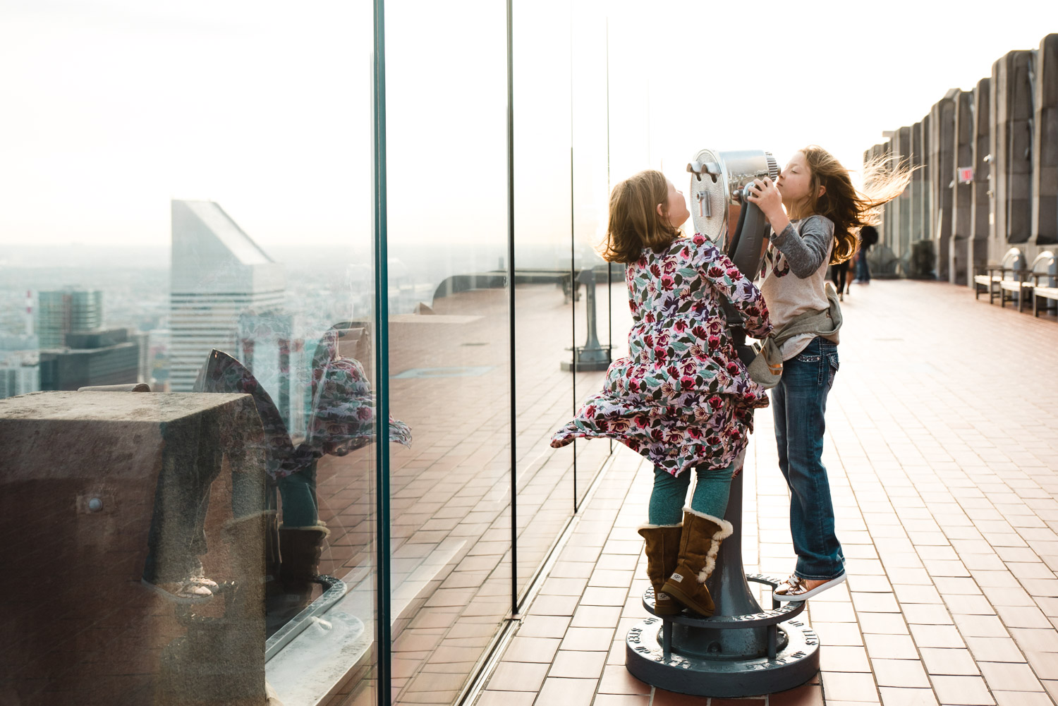 Sisters swinging on a telescope at Top of the Rock.
