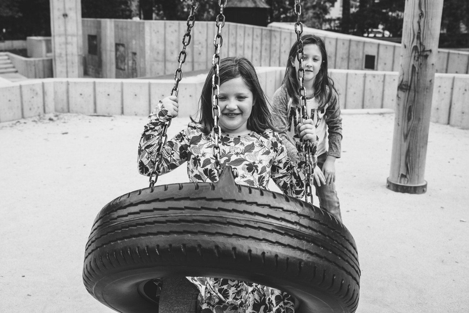 Girls playing on the tire swing in Central Park.
