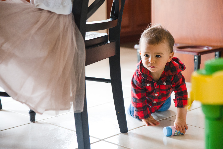 Baby crawling across kitchen floor.