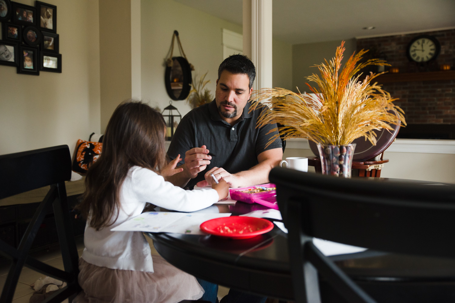 Father drawing with daughter at kitchen table.