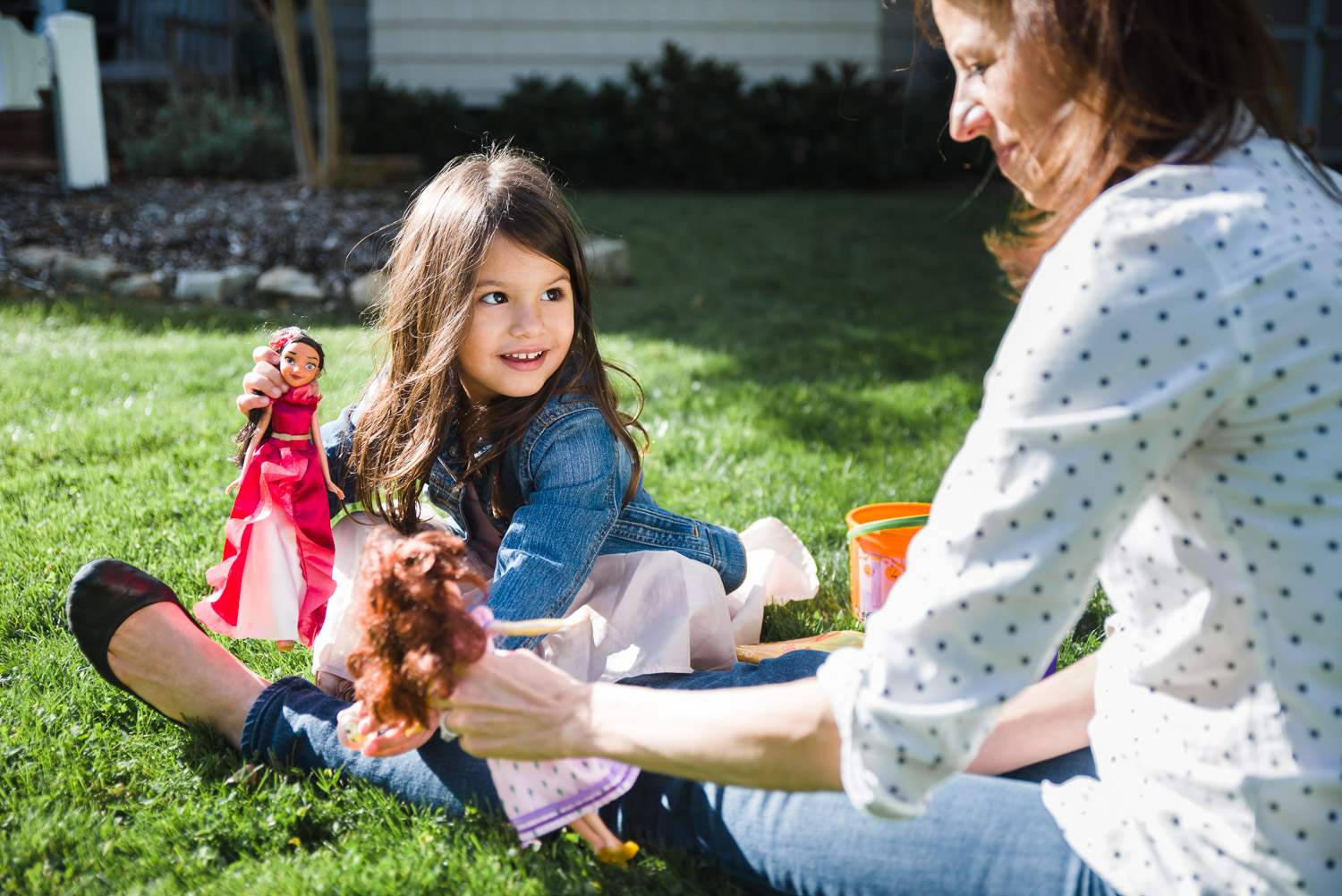 Little girl playing dolls with mother on grass.