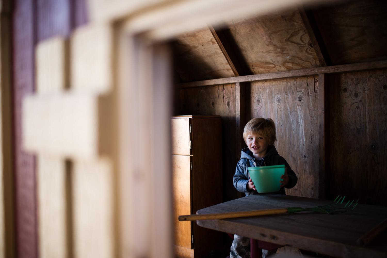 Little boy in playhouse.