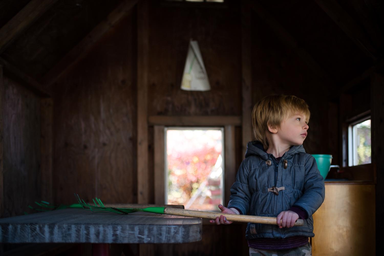 Little boy holding a rake in a playhouse.